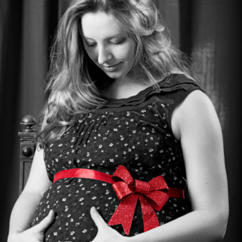 Babybauch mit roter Schleife